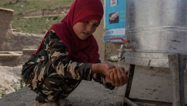 Beta* washes her hands at the newly installed water station. Photo: Stefanie Glinski