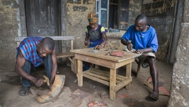 Assa Kamara, Marie Sasay and Isse Conteh fabricating eco stoves from scrap metal.