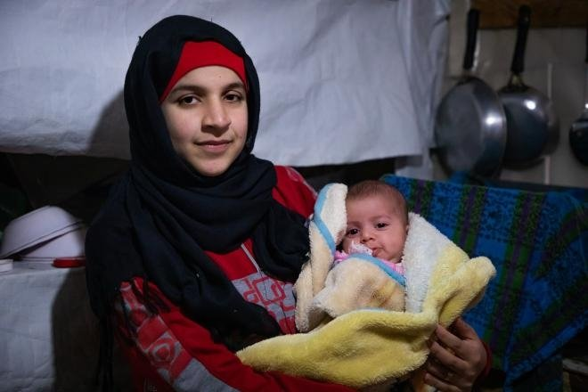 Wafdeh* (20) with her youngest daughter Rajaa* (2 months) in the makeshift kitchen. Concern provide this family with blankets and other materials to make the harsh winter a little more bearably.  Photo: Gavin Douglas/ Concern Worldwide