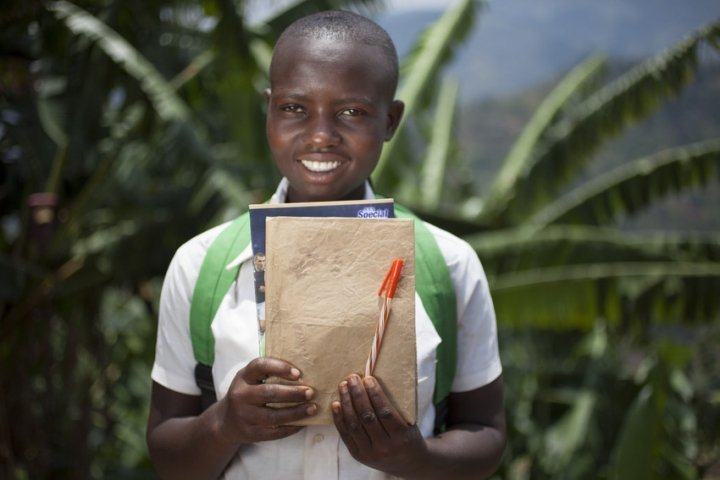 Amida Tuyishimire (14), daughter of Violette Bukeyeneza with her school books and pens for the education she is now able to receive because of the Graduation Programme at her home in Bukinanyana, Cibitoke, Burundi. Photo: Abbie Trayler-Smith / Concern Worldwide