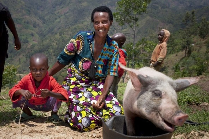 Violette Bukeyeneza (45) and her son Lievain Irankunda 3 (M) with the pig she has bought from the profits of her business at her home in Bukinanyana, Cibitoke, Burundi. She is a beneficiary of the Graduation programme and her business has gone from strength to strength. Photo: Abbie Trayler-Smith / Concern Worldwide