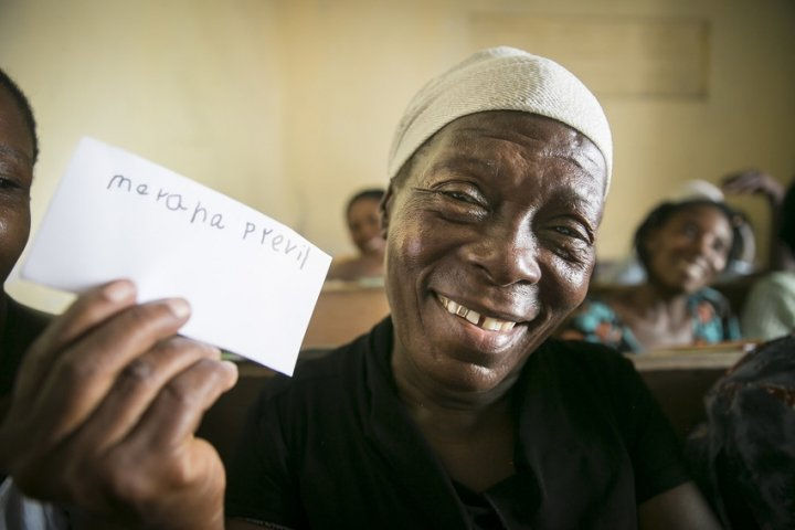 """Merana Previl (63) literacy training course, part of the """"Building Hope & Opportunities in Haiti"""" integrated urban program in Cité Soleil, Port au Prince. Merana has just learned to write her own name. A number of the women taking part have never before attended school. Photo: Kieran McConville/ Concern Worldwide"""