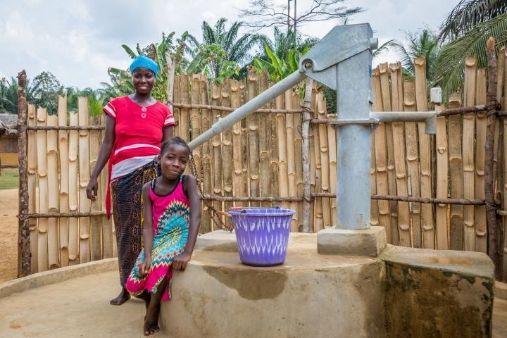 Irene with her daughter Lucy (8). As part of the WASH program, Concern have educated the community on good hygiene practices and installed this water pump. Photo: Gavin Douglas/Concern Worldwide