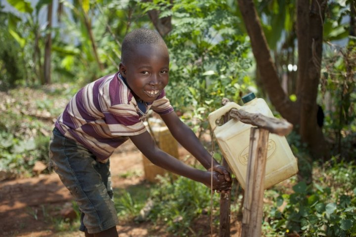 Kevin Niyomuhoza (6) son of Alphonsine Niyonzima (21) with the tippy tap they have installed with the profits of her business. Photo: Abbie Trayler-Smith / Concern Worldwide