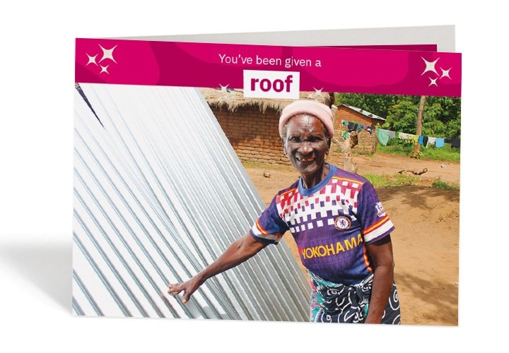 Dorcia, 71, with her brand-new waterproof roof sheets. Photo: Jason Kennedy / Concern Worldwide