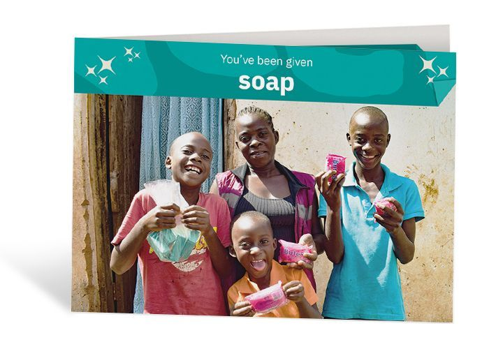 Lizzie and her children Mathews, Given and Trust, with the soap they need to protect themselves. Photo: Concern Worldwide