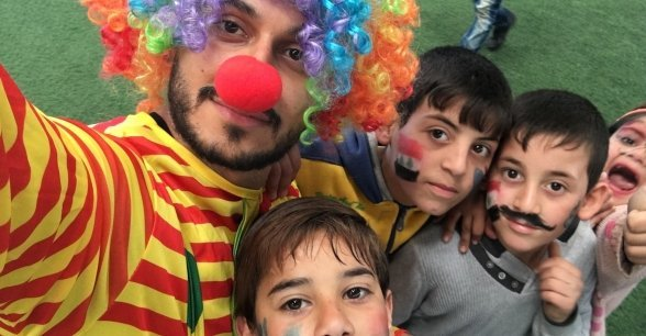 Concern staff member, Abdulrahman Rima, in a clown costume with Syrian children during Global Water Day in a playground in North Lebanon. Photo: AbdulRahman Rima / Concern Worldwide