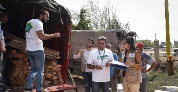 Concern staff organising the distribution of new tent kits (including wood, plastic sheeting etc) to families whose homes were recently burnt down. The tents are going to be built on this field, in Northern Lebanon. Photograph by Mary Turner/Panos Pictures for Concern Worldwide