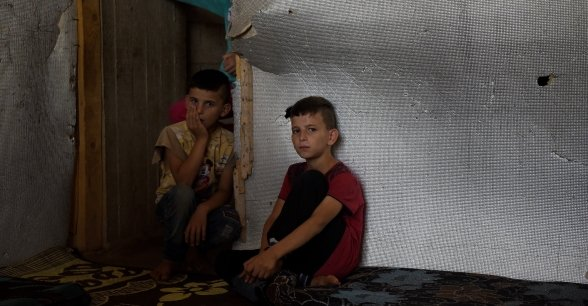 Syrian refugees *Omar,8, and *Bilal, 10, are pictured in the garage which they are currently living, in Northern Lebanon. Photograph by Mary Turner