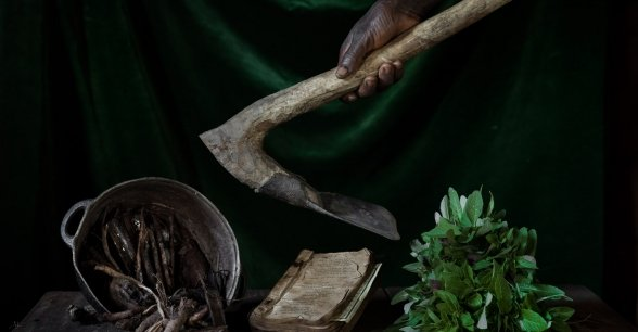 Pictured are Marie's amaranth leaves, pot full of 'termite' wood (used as a traditional cure for stomach ache), a book of religious hymns and hoe. Photo: Chris de Bode