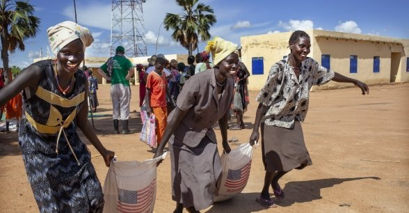 Image shows women collecting food rations from a Concern Worldwide and World Vision food distribution in the Aweil area, South Sudan. Photo: Abbie Trayler-Smith