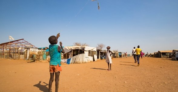 A child flies a home made kite on the streets of Juba's PoC, South Sudan. Photo: Steve De Neef