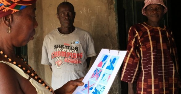 A resident of Bassaia Village Tonkolili District,  Sierra Leone looks at a Covid-19 poster distributed by Concern. Photo: Mohamed Saidu Bah