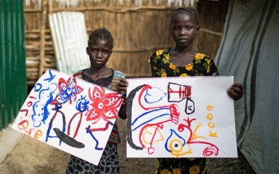 Tapitha Nyasunday and Nhachuodier Liem Tai, participants of Irish artist Brian Maguire's workshop holds up her resulting painting. Photo: Steve De Neef/Concern Worldwide.