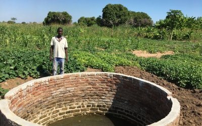 Mr Gerald Action - lead farmer beneficiary of the Nsanje Early Recovery and Resilience Building Project - pictured standing in front of the shallow wells that Concern has rehabilitated with bricks and cement and also treadle pumps and hoses for irrigation of his surrounding crops. Photo: Elias Antoniou / Concern Worldwide