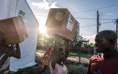 Esparanza Maria, a 25-year-old day worker from Nhamatanda, helps load boxes containing essential household supplies from a warehouse to a truck. Mozambique. Photo: Tommy Trechard