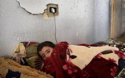 Syrian refugee *Abdel, 7 under a blanket in the garage he and his family are currently living. Photo: Mary Turner