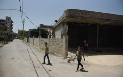 Syrian refugee *Dibeh and her children leave the garage where they are currently living. Photo: Mary Turner