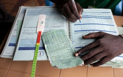 The programme assistant records details of patient visits at a nutrition clinic run by Concern Worldwide in a POC in Juba, South Sudan. Photo: Abbie Trayler-Smith / Concern Worldwide