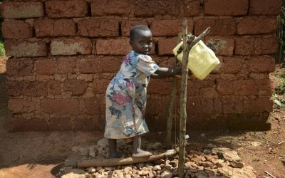 Joella, 5, washes her hands using a tip-tap and soap in Burundi. Photo: Chris de Bode