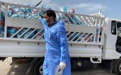 A man in a mask distributes hygiene kits