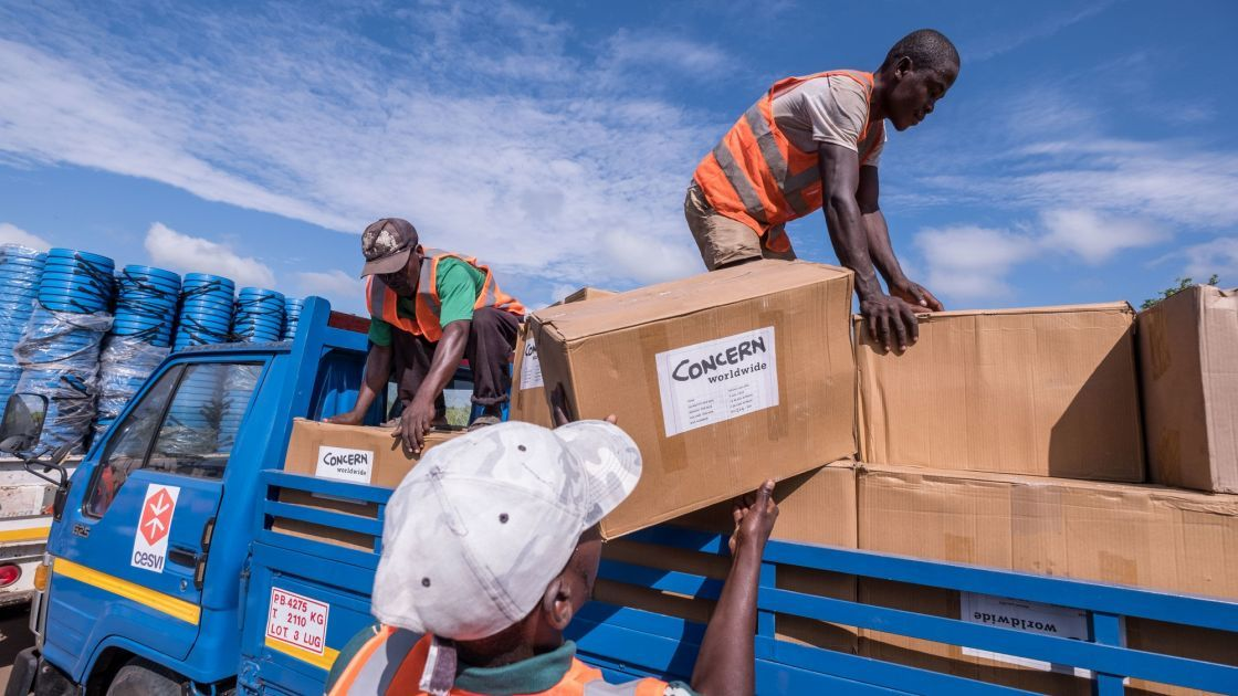 Workers unload kitchen kits from a truck at a distribution in Ndeja, Mozambique, which was hard hit by cyclone Idai in March 2019. Photo: Tommy Trenchard / Concern Worldwide