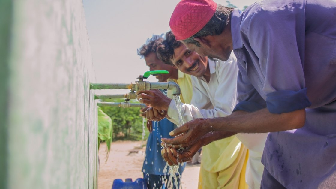 Two local men, Naaju and Rajesh are talking to each other happily while drinking water from water plant installed by Concern Worldwide. Photo: Black Box Sounds/ Concern Worldwide.