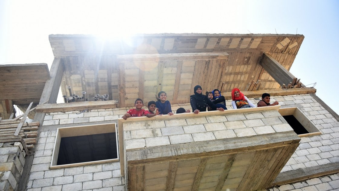 Syrian refugees lean out of the balcony of the home in Northern Lebanon where Concern will be putting in doors and windows into the family's home. Photograph by Mary Turner
