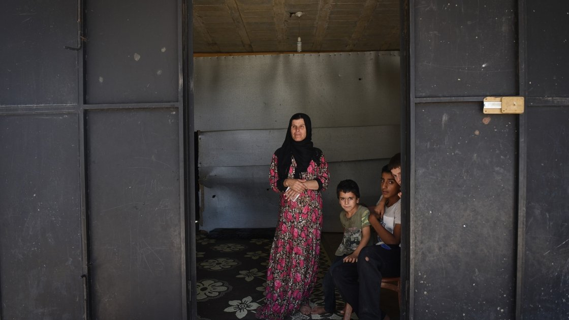 Syrian refugee *Dibeh, 41, and her children *Bilal, 10, *Abdel, 7, and *Omar 8, are pictured in the garage where they are currently living. Photograph by Mary Turner