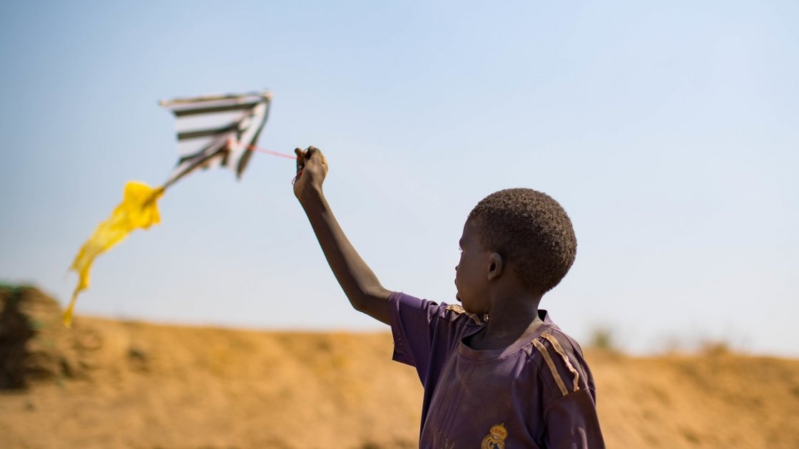 A child flies a home made kite on the streets of Juba's PoC, South Sudan. Photo: Steve De Neef / Concern Worldwide.
