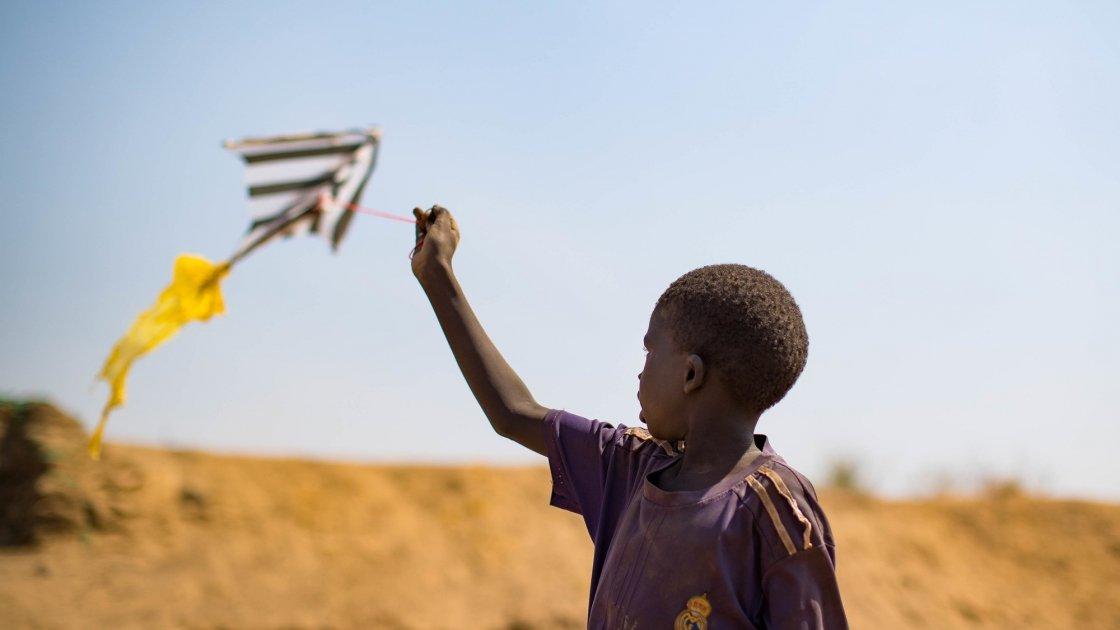 A child flies a home made kite on the streets of Juba's PoC, South Sudan. Photo: Steve De Neef / Concern Worldwide.