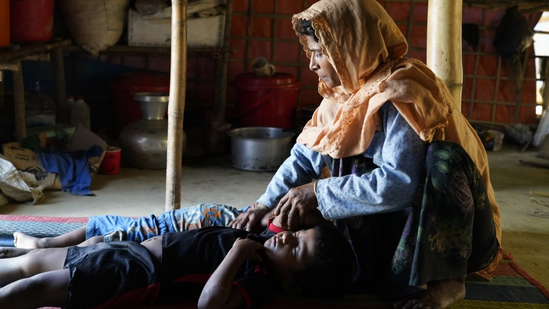 Menara* (40), one of the beneficiary sits beside her sleeping sons at her tent at Jamtoli, Ukhiya. Photo: Abir Abdullah/Concern Worldwide