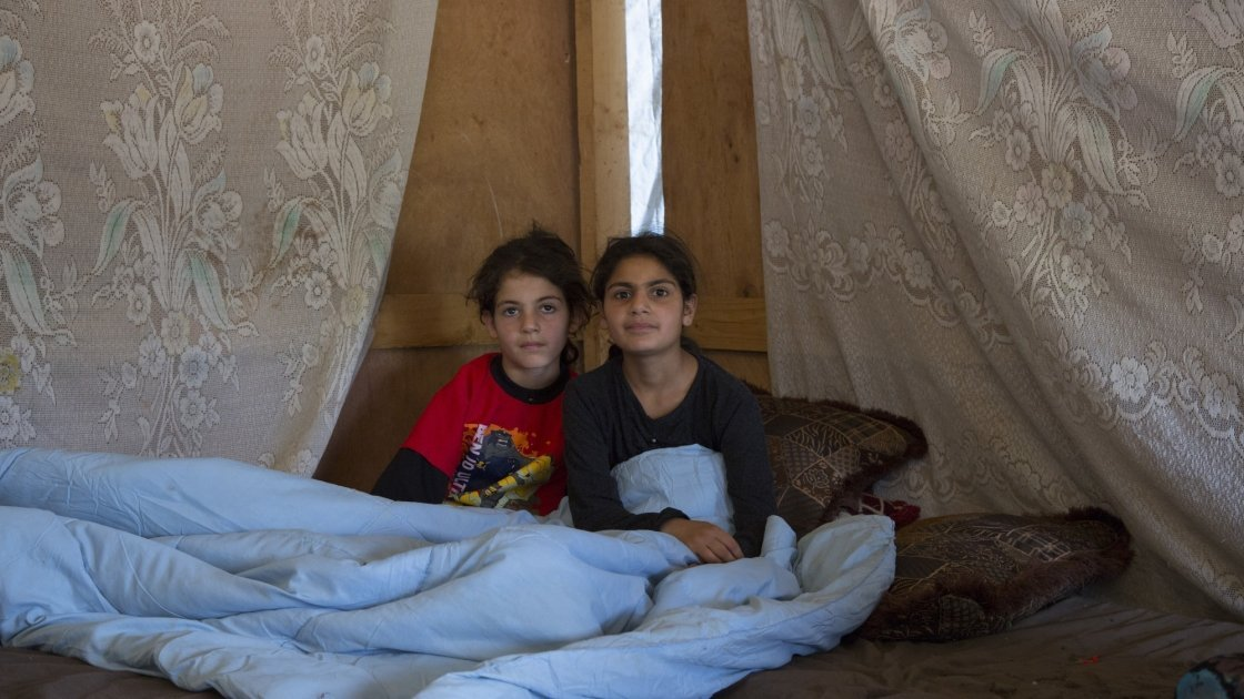 Two Syrian refugee children sit under a duvet