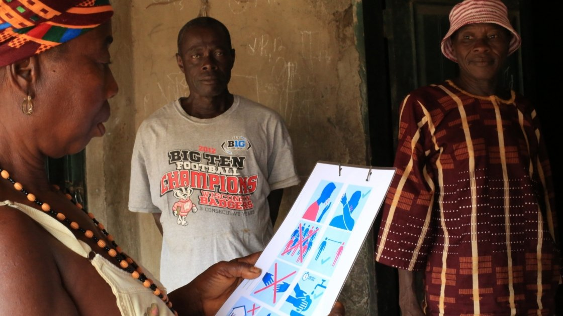 A resident looks at a Covid-19 poster distributed by Concern after an awareness session. Photo: Mohamed Saidu Bah