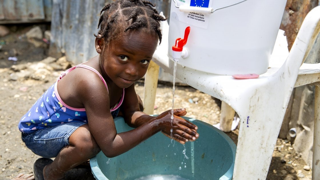 Cherica, two, washes her hands in Haiti