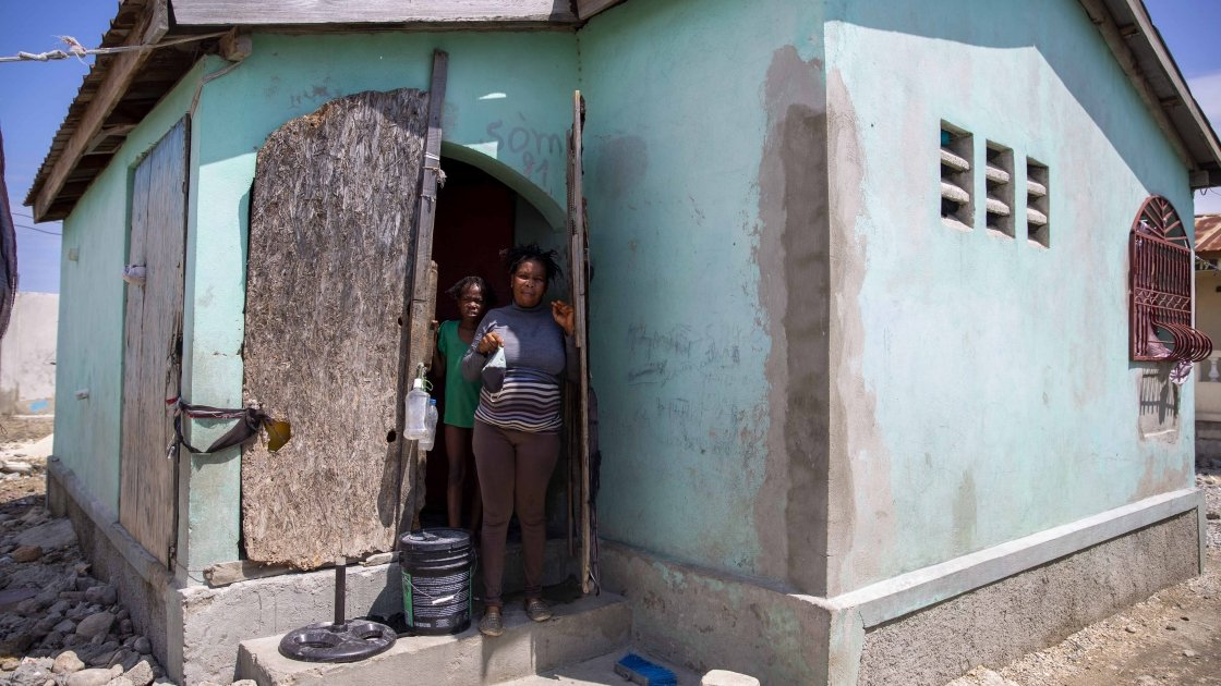 Roseline, a dressmaker from Haiti, outside her home with her son