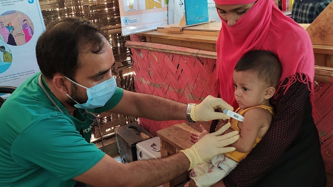 A paramedic is checking the temperature of 8 month old, Arman* in Cox's Bazar, Bangladesh. Photo: Rajib Kumar Kundu