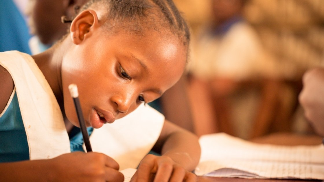 A Class 3 pupil at Baptist Rowalla Primary School, in Tonkolili, Sierra Leone, engages in a literacy exercise, 2014. Photo: Michael Duff / Concern Worldwide.