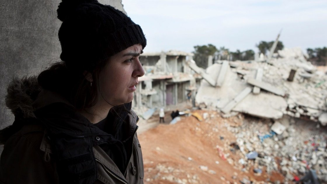 A young Syrian girl stares out at rubble