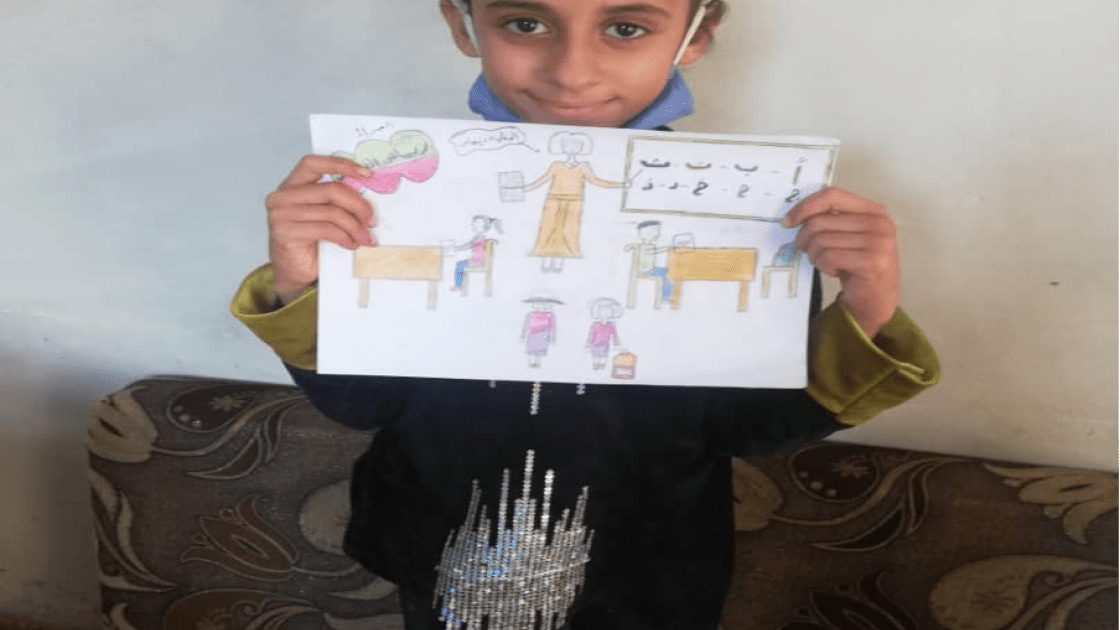 10-year-old Fatima from Syria pictured with her drawing of what she wants to be when she grows up.