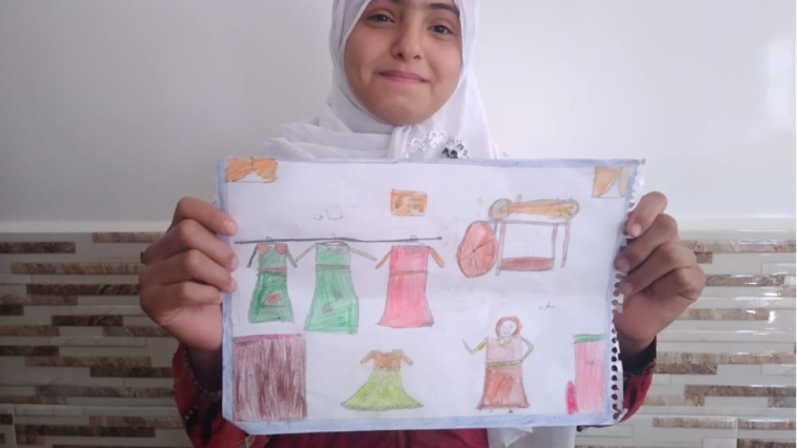 12-year-old Khaled from Syria pictured with her drawing of what she wants to be when she grows up: a tailor.