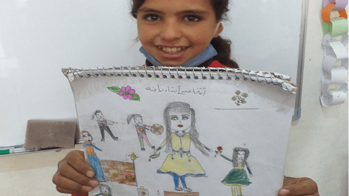 12-year-old Samira from Syria pictured with her drawing of what she wants to be when she grows up.