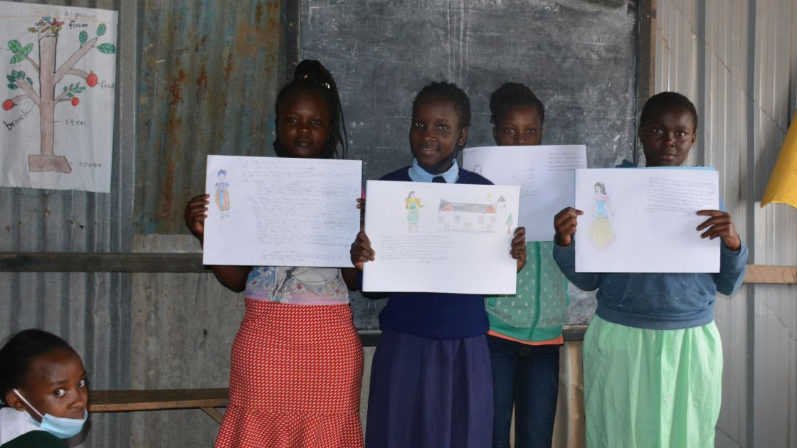 The class of a primary school in Kenya holding up their drawings of their hopes and ambitions.