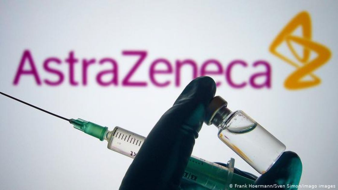 A gloved hand holds up a syringe and a vaccine vial in front of the AstraZeneca logo