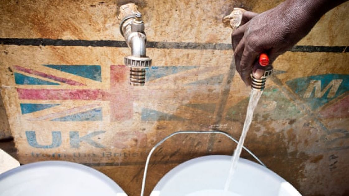 A hand runs a tap against the background of a UK aid logo