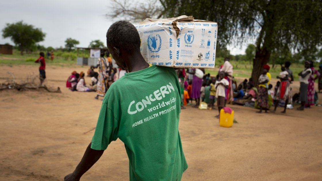 A man in a Concern vest carries supplies at a nutrition clinic in South Sudan