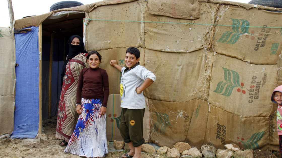 Azmat and two of her four children stand outside their makeshift shelter in an informal tented settlement in Akkar district, north Lebanon.