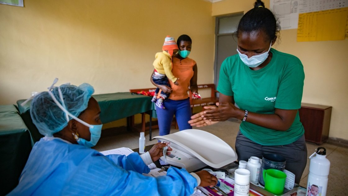 Jane Wanjiru has brought her baby son Mark Moses (11 months old) to Mukuru Health Centre. Facility staff Damaris Too (green t-shirt) and Nutritionist Angela Mtiini (wearing gown) assess Mark Moses Photo: Ed Ram / Concern Worldwide