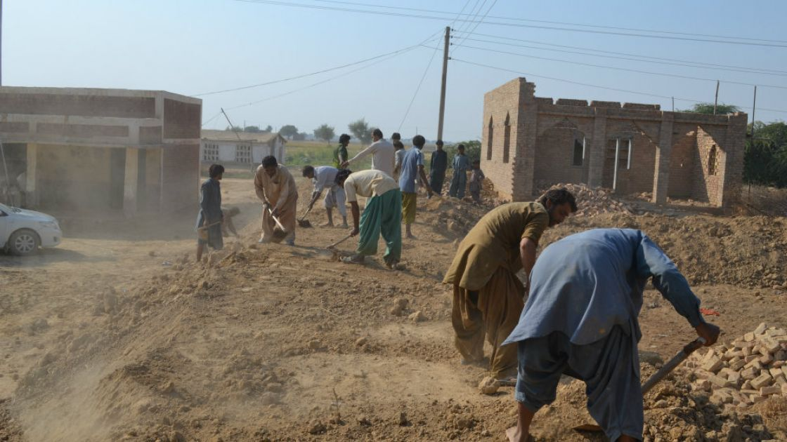 People in Pakistan building an embankment to protect their community from flooding. Credit: Qurban Ali/Bright Star Development Society