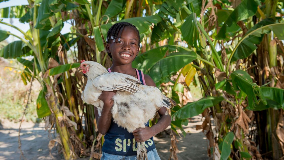 Joyce, 8, holds a chicken that was provided as part of Concern's RAIN programme to her mother Lillian Shachinda in Zambia. Photo: Gareth Bentley / Concern.